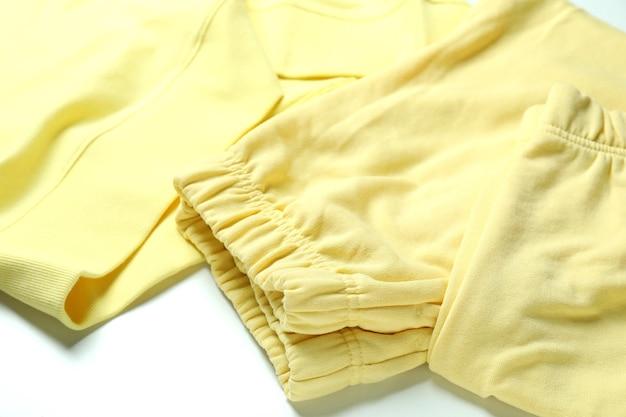白い背景の上の黄色のスウェットシャツとスウェットパンツ