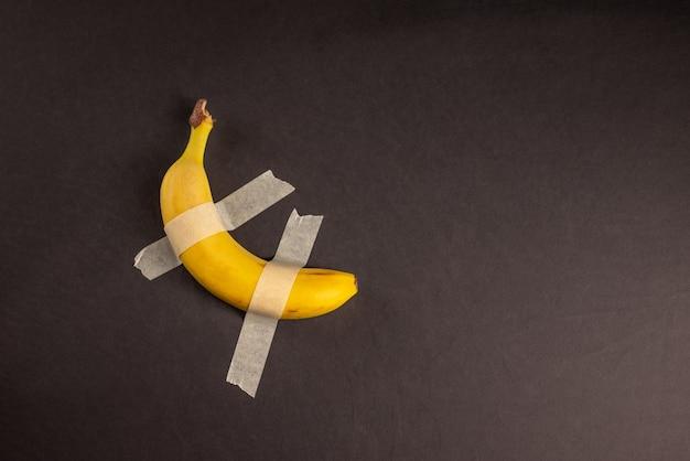 壁に黄色い甘いバナナ。白い壁にテープで留められたバナナダクト。