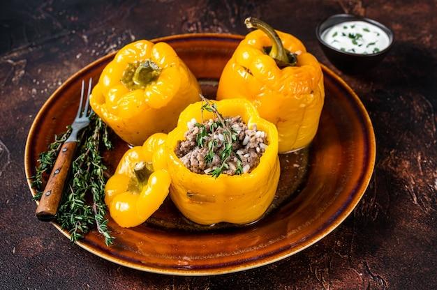 Желтый сладкий болгарский перец, фаршированный мясом, рисом и овощами. темный фон. вид сверху.