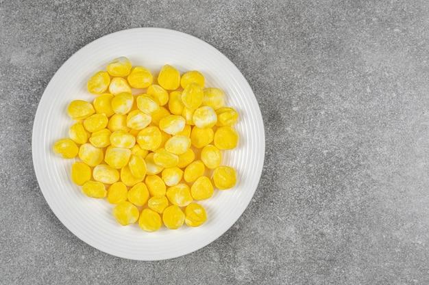 Желтые сладкие конфеты в белой тарелке