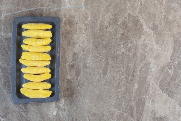 Yellow sweet candies in a row on wooden board.