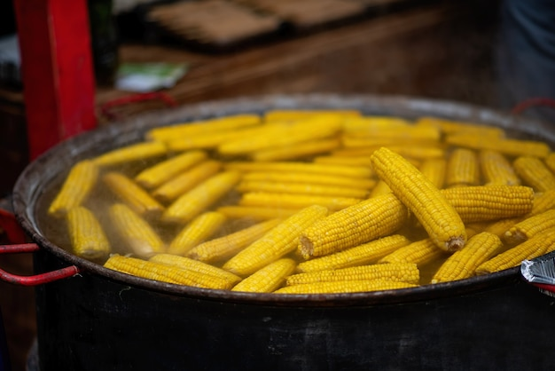 Yellow, sweet corn is cooked on the bone in a large aluminum iron cauldron. summer camping food. light snack.