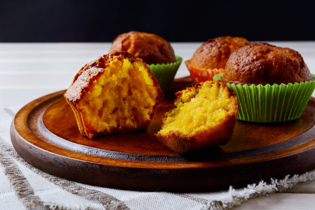 Yellow sweet pumpkin muffins served on the wooden tray