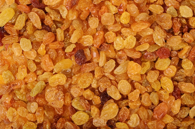 Yellow sweet raisins as abstract delicious background texture