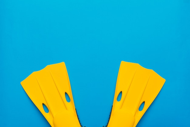 Yellow swimming flippers on blue