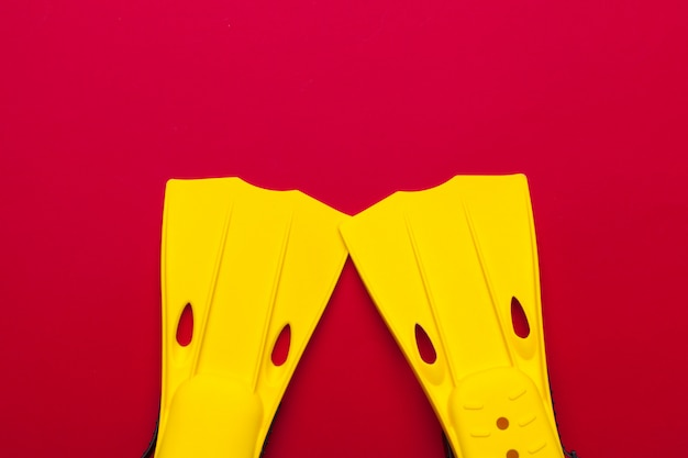 Yellow swimming flippers on colored