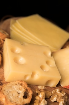 Yellow swiss cheese with bread slice and walnut on wooden surface