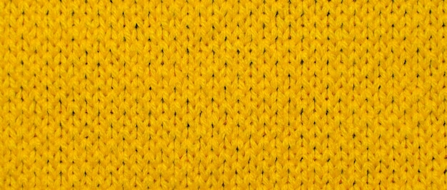 노란색 합성 니트 직물을 닫습니다. 니트 직물 질감 배경