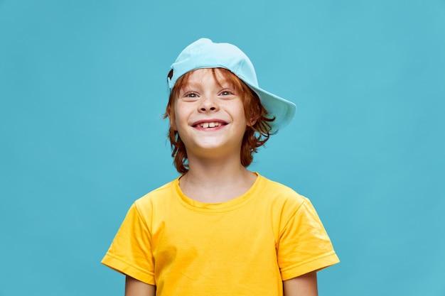 男の子の笑顔の頭に黄色のtシャツキャップ