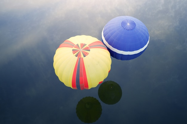 Yellow tabloid balloons over blue water, view from above, drone shooting.