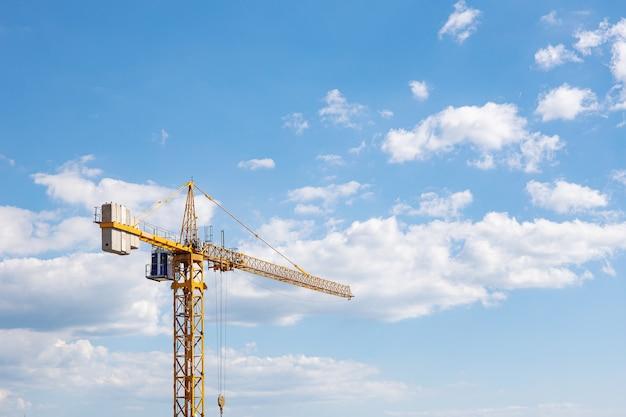 青い空と雲を背景に黄色の背の高い建設用クレーン。