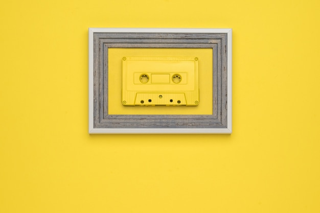 A yellow tape cassette in a frame on a yellow background. flat lay.