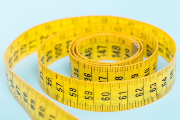 Yellow tape measure on blue background