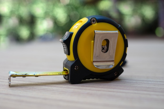 Yellow tape measure on wooden board at blurred background