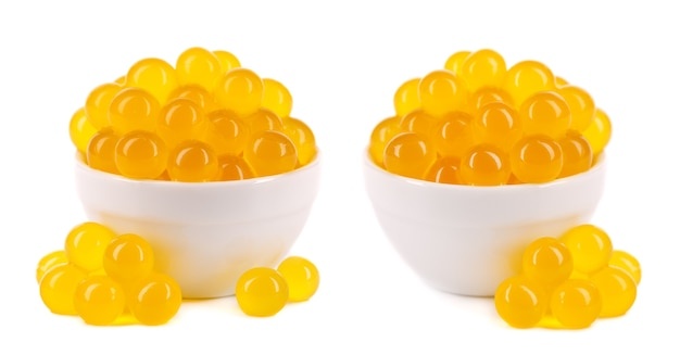 Yellow tapioca pearls for bubble tea isolated on white background. tapioca pearls in ceramic bowl.