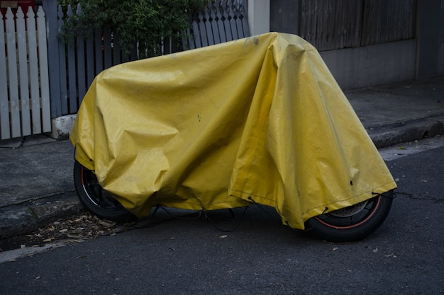 Yellow tarp cover over a parked motorcycle on the street