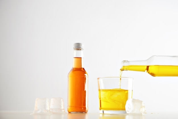 노란색 맛있는 레모네이드 음료가 오렌지 음료와 함께 밀폐 된 라벨이없는 병 근처에 얼음 조각으로 병에서 유리로 쏟아집니다.