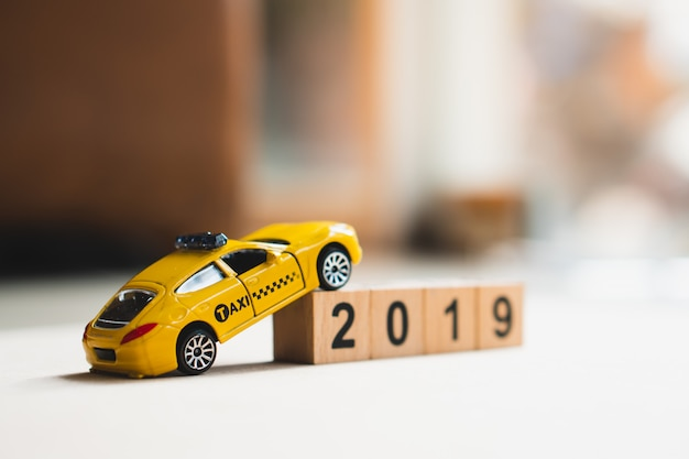 Yellow taxi run around wooden block year 2019 using as transportation concept