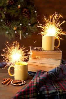 반짝임과 크리스마스 배경이 있는 노란색 찻잔, 내부에 밝은 빛이 있는 세라믹 컵, 두루마리와 계피가 있는 책과 담요