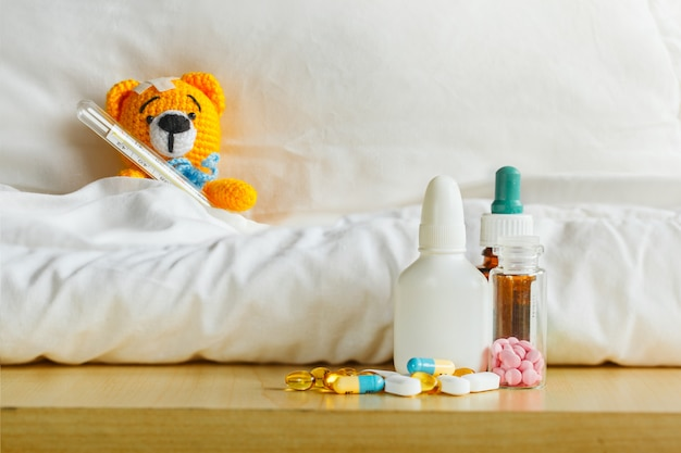 Yellow teddy bear with thermometer and plaster on head in white bedroom and medicament on a table