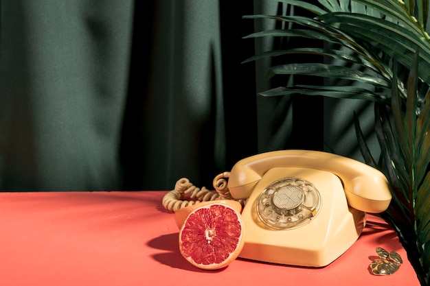 Yellow telephone next to grapefruit on table