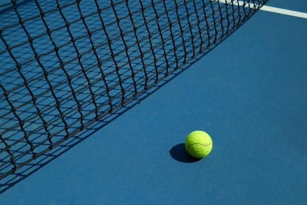 노란색 테니스 공은 검은 테니스 코트의 그물 근처에 누워 있습니다.
