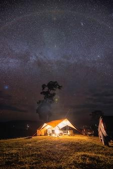 Желтая палатка-кемпинг сияет на холме под млечным путем и звездно в ночном небе
