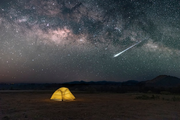 Yellow tent under milky way galaxy with meteor in desert in the countryside of northern thailand, stars above the night mountain forest and a glowing camping tent.