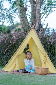 自然の中でかわいい女の子がいる黄色いテント