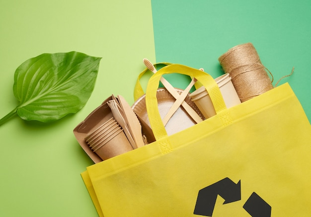 Yellow textile bag and disposable tableware from brown craft paper