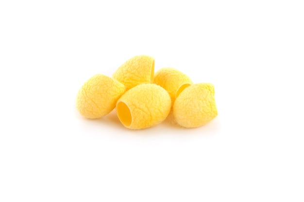 Yellow thai silkworm cocoons pile isolated on white surface.