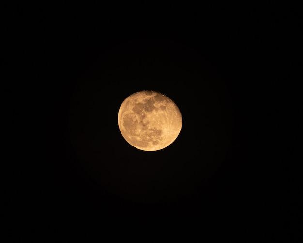 Желтая луна светится неровной текстурой в ночном небе
