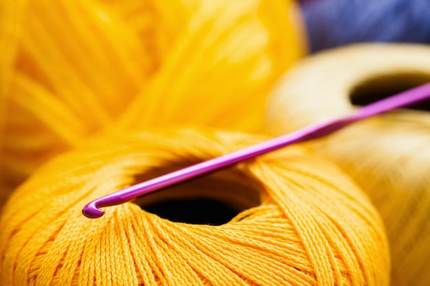 Yellow thread with crochet close-up, handiwork surface