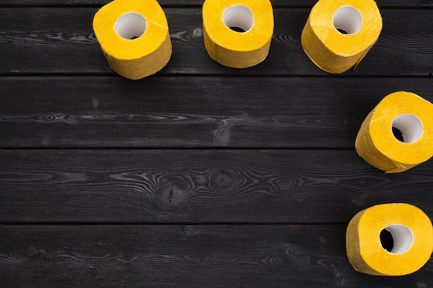 Yellow toilet paper on black wooden background top view