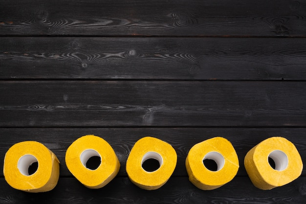 Yellow toilet paper on black wooden table top view