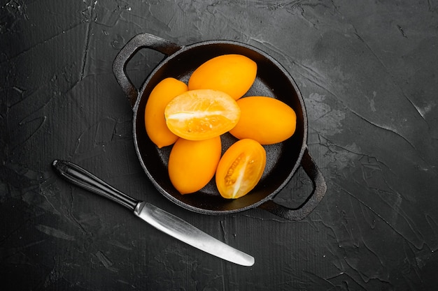 검은색 짙은 돌 탁자 배경에 있는 노란색 토마토 세트, 평면도