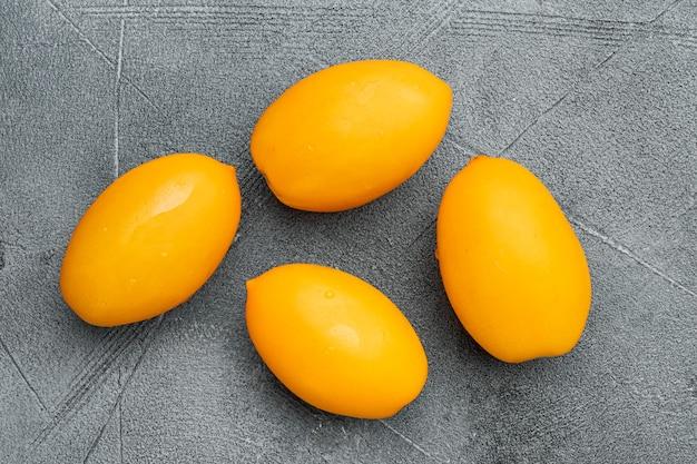 회색 돌 테이블 배경에 노란색 토마토 세트, 평면도