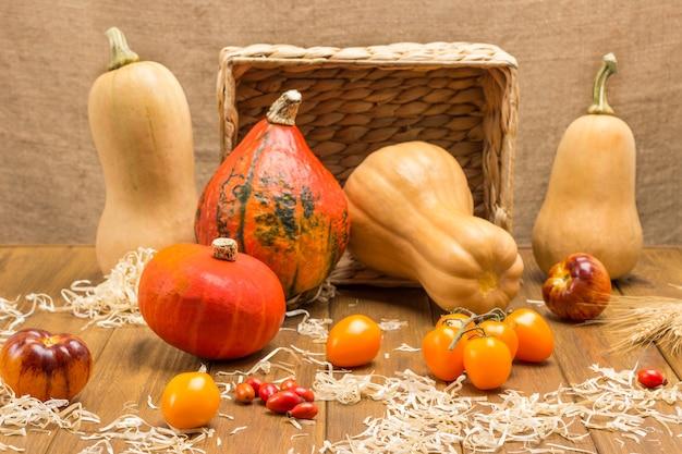 藁の中に黄色いトマトとローズヒップ。熟したカボチャと籐のバスケット。木製の背景。