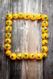Pomodori gialli che formano una cornice rettangolare su uno sfondo di legno scuro. vista dall'alto.