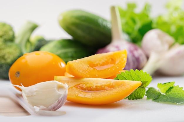 Желтые помидоры, чеснок и другие овощи на белом