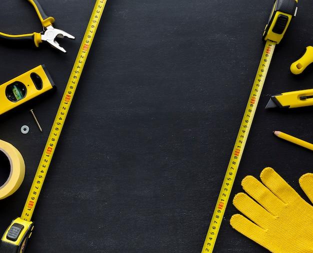 Желтые инструменты и строительные перчатки с копией пространства