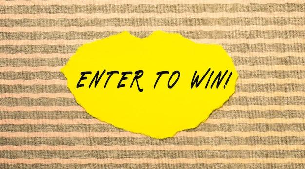 Желтая рваная бумага с надписью enter to win на серо-розовой поверхности