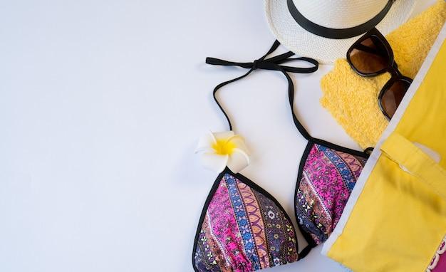 흰색 바탕에 노란색 수건, 선글라스, 비키니 상의, 모자, 꽃