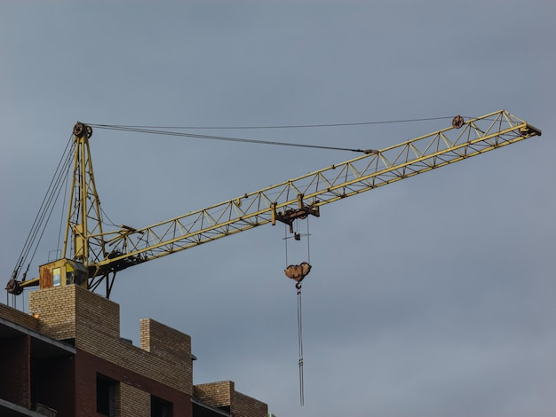 Yellow tower crane on the background of a building under construction