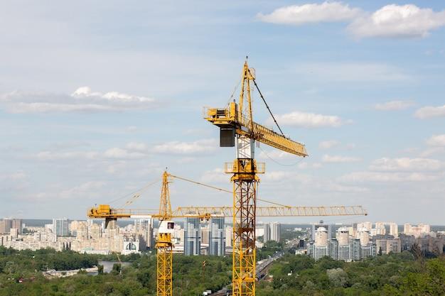 다층 주택 배경의 건설 현장에서 노란색 타워 크레인