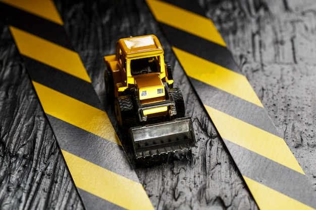 Yellow toy bulldozer. black and yellow fence tape