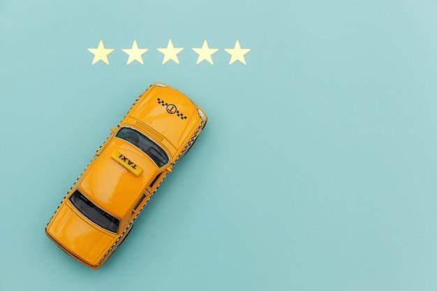 Желтый игрушечный автомобиль и рейтинг 5 звезд на синем фоне
