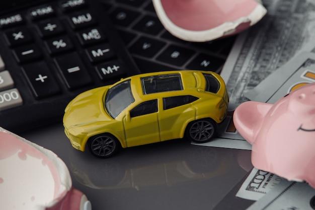 Желтый игрушечный автомобиль крупным планом и долларовые банкноты с разбитой розовой копилкой. страховая концепция
