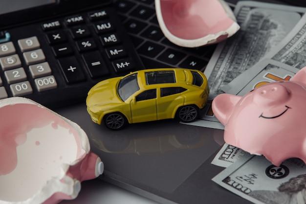Желтый игрушечный автомобиль крупным планом и долларовые купюры со сломанной розовой копилкой