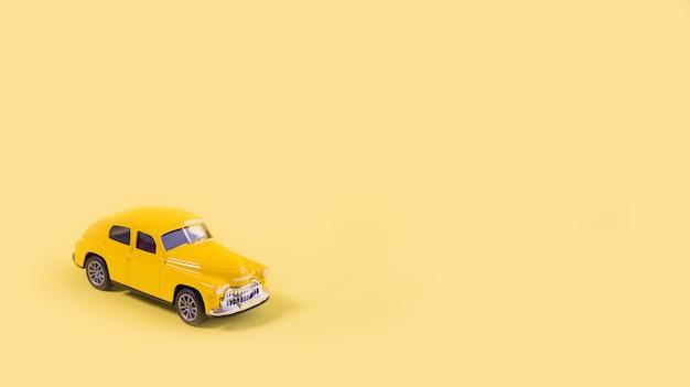 Желтый игрушечный автомобиль, изолированные на желтом фоне с копией пространства